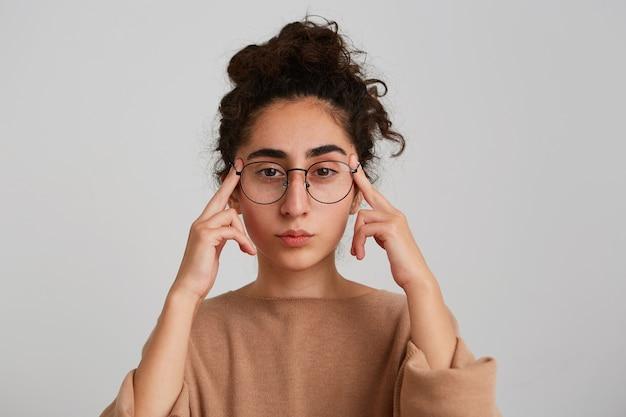 Retrato de uma jovem georgiana, pensativa e concentrada, com cabelo encaracolado, usa uma camisola bege e óculos tocando suas têmporas e pensando isolado sobre uma parede branca Foto gratuita
