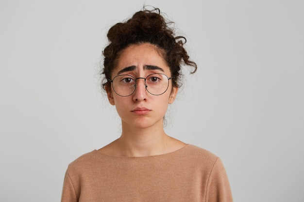 Retrato de uma jovem georgiana triste, com cabelo encaracolado, usa um pulôver bege e óculos se sente infeliz e frustrado isolado sobre uma parede branca Foto gratuita