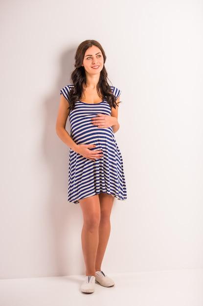 Retrato de uma jovem grávida em um vestido listrado. Foto Premium