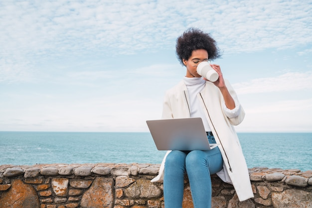 Retrato de uma jovem latina usando seu laptop e bebendo uma xícara de café enquanto está sentado contra o mar Foto Premium