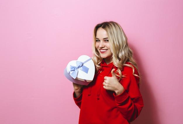 Retrato de uma jovem loira bonita animado segurando um presente e feliz sobre parede rosa Foto Premium