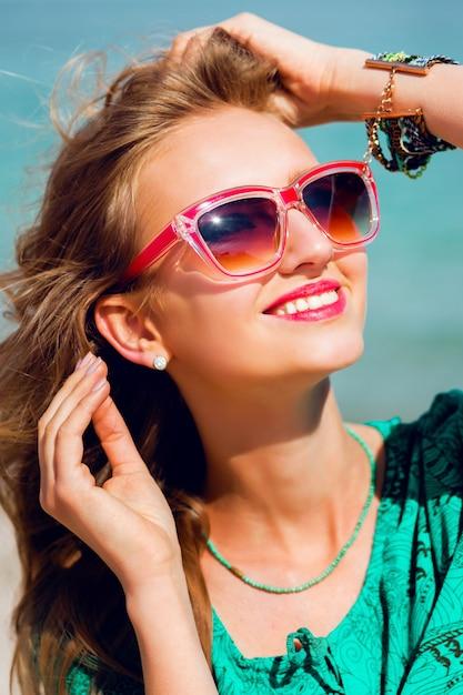 Retrato de uma jovem loira linda em óculos de sol, posando na ensolarada praia tropical Foto gratuita