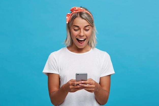 Retrato de uma jovem loira surpresa e feliz com a boca aberta usando uma camiseta branca Foto gratuita