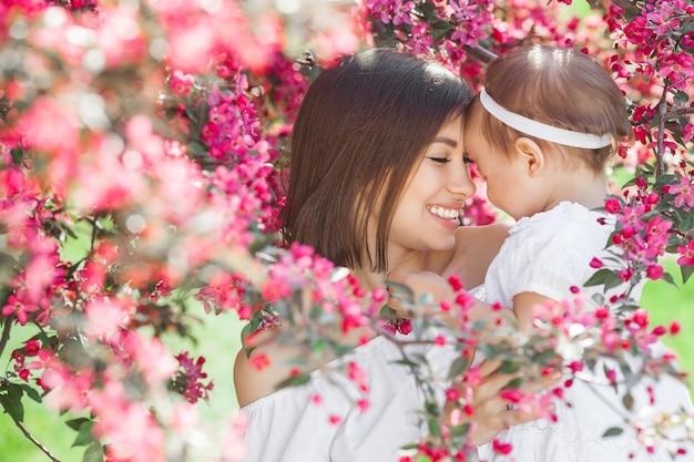 Retrato de uma jovem mãe linda com sua filhinha. close-up ainda de amar a família. mulher atraente, segurando seu filho em flores cor de rosa e sorrindo. Foto Premium