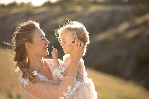 Retrato de uma jovem mãe linda mantém sua amada filha nos braços Foto Premium