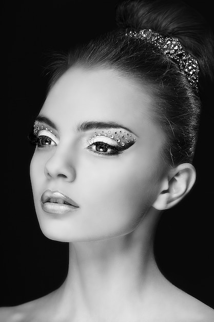 Retrato de uma jovem muito bonita com maquiagem moda isolada em preto Foto Premium