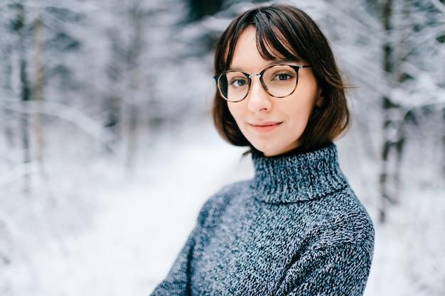 Retrato de uma jovem muito bonita em copos no bosque nevado. Foto Premium
