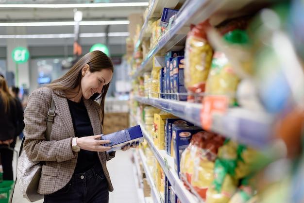 Retrato de uma jovem mulher ao lado do supermercado lê um rótulo de macarrão na embalagem Foto Premium