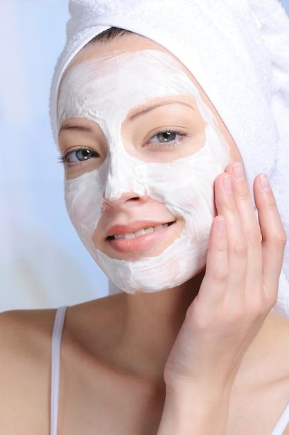Retrato de uma jovem mulher atraente com máscara cosmética no rosto Foto gratuita