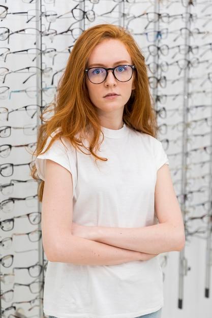 Retrato de uma jovem mulher atraente, de pé na loja de óptica, com o braço cruzado Foto gratuita