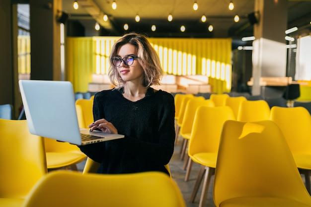 Retrato de uma jovem mulher atraente, sentado na sala de aula, trabalhando no laptop usando óculos, aluno aprendendo na sala de aula com muitas cadeiras amarelas Foto gratuita