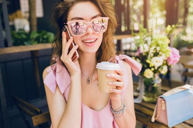 Retrato de uma jovem mulher atraente, sentado no café, roupa de moda de verão, vestido de algodão rosa, óculos de sol, sorrindo, bebendo café, acessórios elegantes, roupas da moda, falando no telefone Foto gratuita