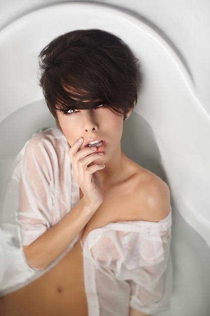 Retrato de uma jovem mulher bonita com cabelo curto, desfrutando de banho em camisa de homem branco tocando os lábios Foto gratuita