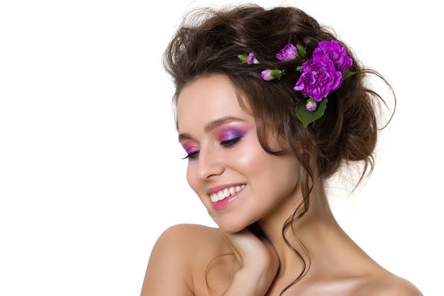Retrato de uma jovem mulher bonita com flores violetas no cabelo Foto Premium