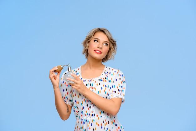 Retrato de uma jovem mulher bonita com perfume sobre parede azul Foto gratuita