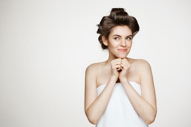Retrato de uma jovem mulher bonita em rolos de cabelo e toalha sorrindo posando. cosmetologia e spa. Foto gratuita