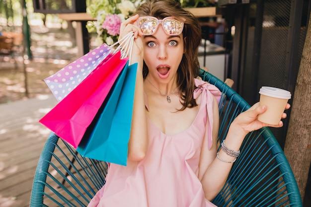 Retrato de uma jovem mulher bonita feliz sorrindo com expressão de rosto surpreso, sentado no café com sacolas de compras, bebendo café, roupa de moda verão, vestido de algodão rosa, vestuário da moda Foto gratuita