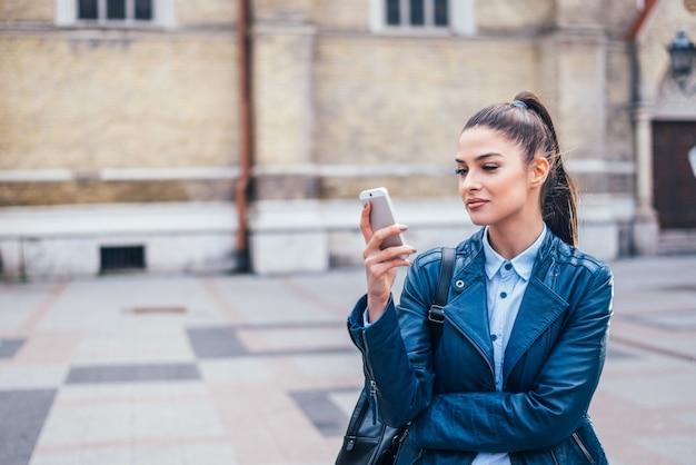 Retrato de uma jovem mulher bonita no casaco de cabedal que olha o smartphone. Foto Premium