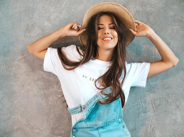 Retrato de uma jovem mulher bonita olhando. menina na moda em roupas de verão casual macacão e chapéu. Foto gratuita