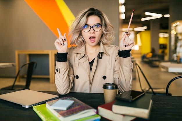 Retrato de uma jovem mulher bonita, tendo uma idéia, sentado à mesa no casaco trabalhando no laptop no escritório colaborador, usando óculos, ocupado, pensando, problema Foto gratuita