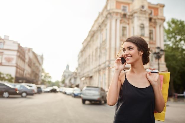 Retrato de uma jovem mulher caucasiana bonita com cabelo escuro no vestido preto, acordando em torno da cidade Foto gratuita