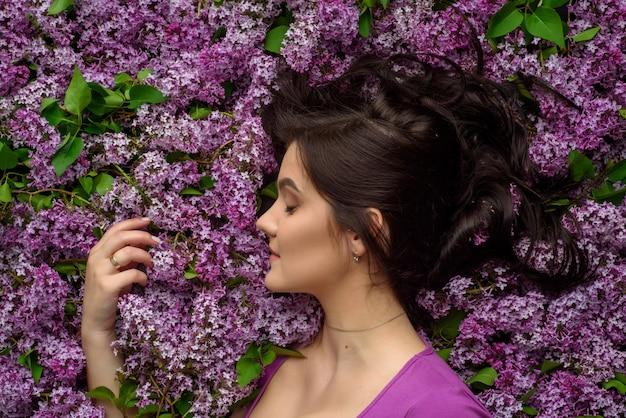 Retrato de uma jovem mulher cercada por lilases. uma mulher está de pé de lado. Foto Premium