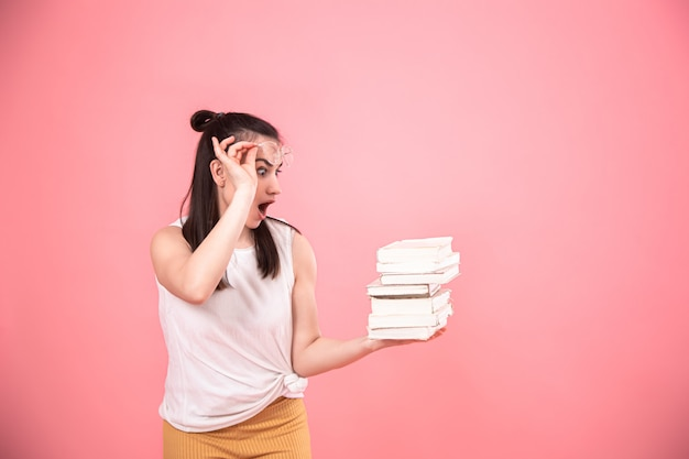 Retrato de uma jovem mulher com óculos em um fundo rosa com livros nas mãos dela. Foto gratuita