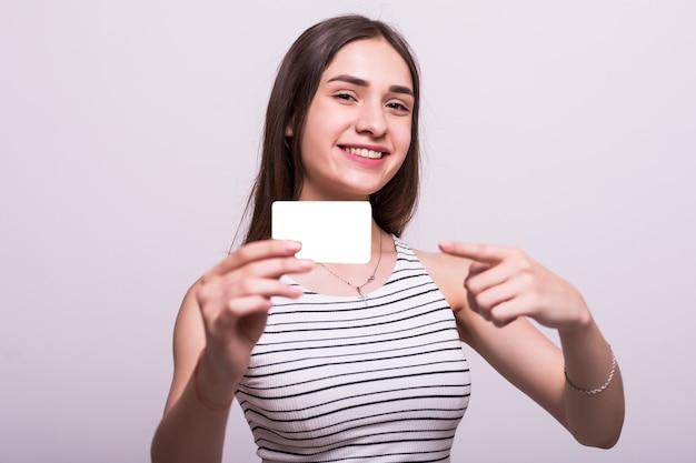 Retrato de uma jovem mulher de negócios sorridente vestido bege segurando o cartão de crédito vazio no fundo cinza Foto gratuita