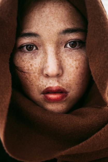 Retrato de uma jovem mulher do cazaquistão com sardas cobertas por um cobertor marrom Foto gratuita