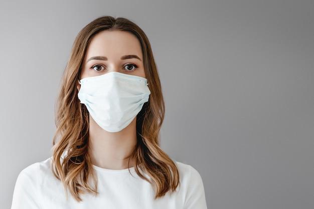 Retrato de uma jovem mulher em uma máscara médica isolada sobre fundo cinza. paciente jovem fica contra o fundo da parede, copie o espaço para texto Foto Premium