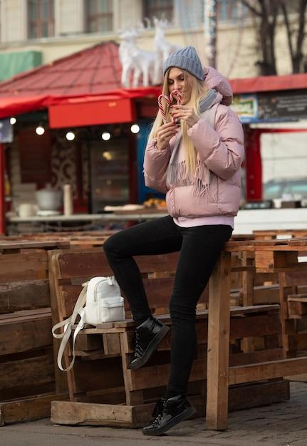 Retrato de uma jovem mulher feliz bonita com doces posando na rua de uma cidade europeia. natal. Foto Premium