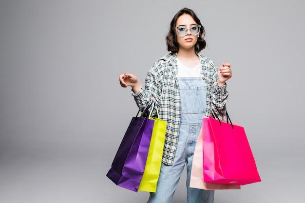 Retrato de uma jovem mulher feliz e sorridente em óculos de sol com sacolas de compras isoladas em cinza. conceito de venda. Foto gratuita