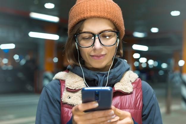 Retrato de uma jovem mulher feliz ouvindo música em um smartphone Foto Premium