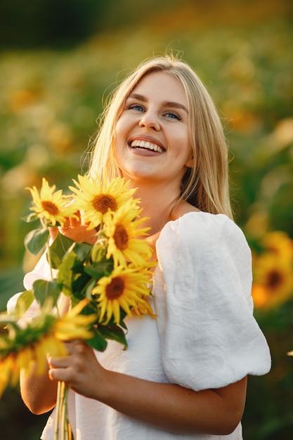 Retrato de uma jovem mulher loira bonita no campo de girassóis na luz de fundo. conceito de campo de verão. mulher e girassóis. luz de verão. beleza ao ar livre. Foto gratuita
