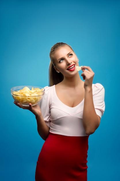 Retrato de uma jovem mulher loira comendo batatas fritas e segurando uma tigela de vidro Foto Premium