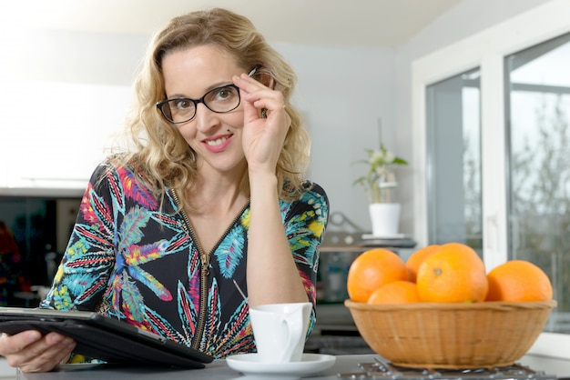 Retrato de uma jovem mulher loira na cozinha com computador tablet Foto Premium