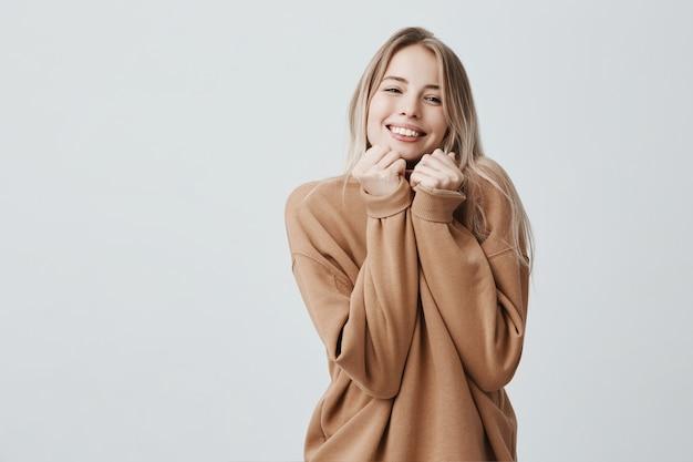 Retrato de uma jovem mulher loira tem expressão alegre sonhadora, vestindo blusa quente solta Foto gratuita
