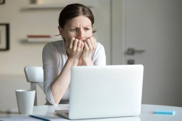 Retrato de uma jovem mulher na mesa com laptop, medo Foto gratuita