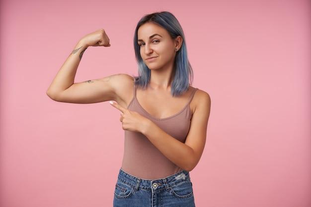 Retrato de uma jovem mulher tatuada com corte de cabelo curto apontando na mão levantada enquanto mostra seus bíceps fortes, em pé na rosa Foto gratuita