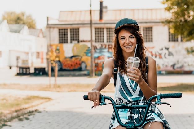 Retrato de uma jovem mulher urbana bonita com uma bicicleta. Foto Premium