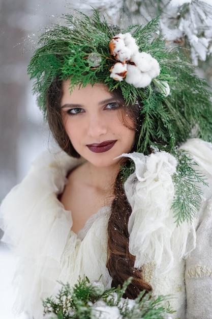Retrato de uma jovem noiva linda com um buquê. cerimônia de casamento de inverno. Foto Premium