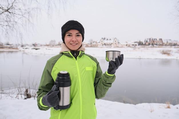Retrato de uma jovem positiva com uma jaqueta verde segurando uma garrafa térmica e bebendo chá quente no lago de inverno Foto Premium
