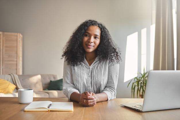 Retrato de uma jovem professora de pele escura, confiante e positiva, com penteado volumoso, se preparando para a aula online, sentada à mesa com laptop, café e caderno no interior do escritório em casa Foto gratuita