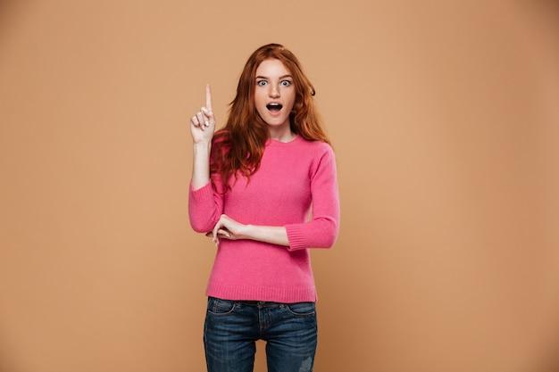 Retrato de uma jovem ruiva animado apontando para cima com os dedos Foto gratuita