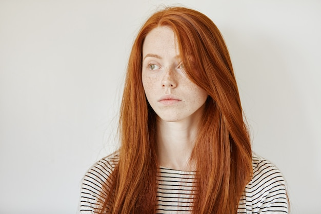 Retrato de uma jovem ruiva bonita caucasiana com sardas e cabelos longos soltos posando Foto gratuita