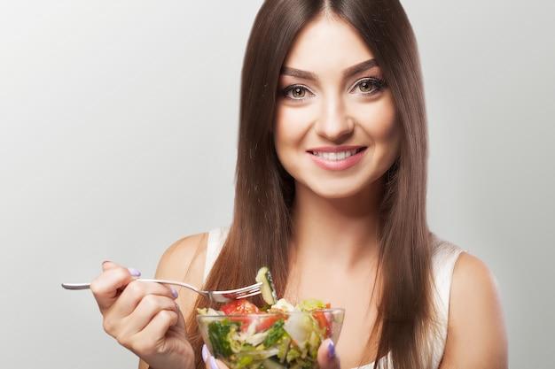 Retrato de uma jovem sorridente com salada de legumes vegetariano. estilo de vida saudável. comida saudável. Foto Premium