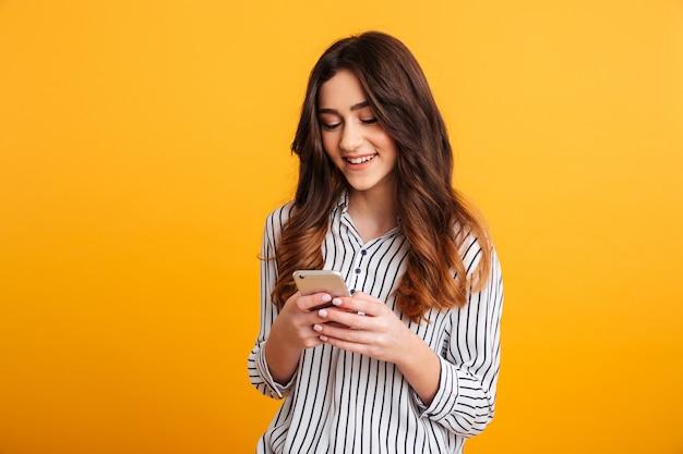 Retrato de uma jovem sorridente, usando telefone celular Foto gratuita