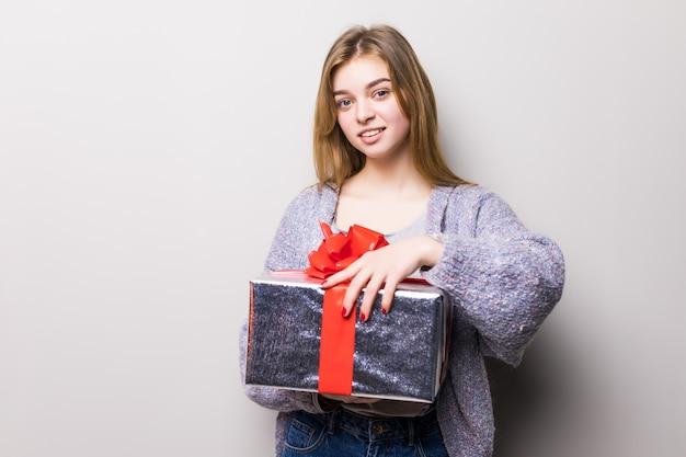 Retrato de uma linda garota adolescente sorridente abrindo uma caixa de presente isolada Foto gratuita