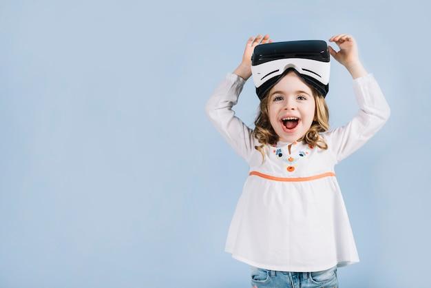 Retrato de uma linda garota animada com fone de ouvido de realidade virtual contra o pano de fundo azul Foto gratuita