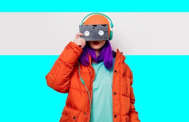 Retrato de uma linda garota com cabelo roxo no chapéu laranja e jaqueta e com fones de ouvido e fita vhs em fundo branco e azul. estilo moderno Foto Premium